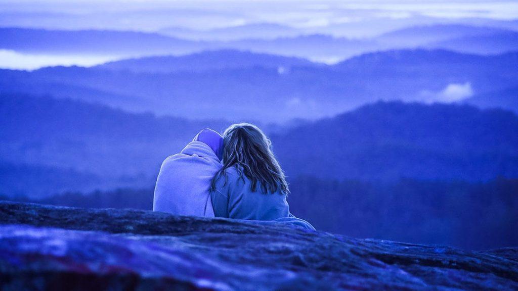 Couple assis l'un à coté de l'autre devant un paysage de montagne. Union, pacs.