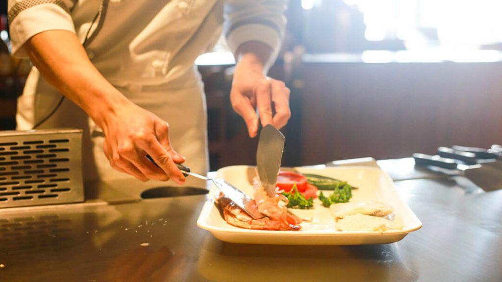 Cuisinier préparant un repas. Portage de repas à domicile.