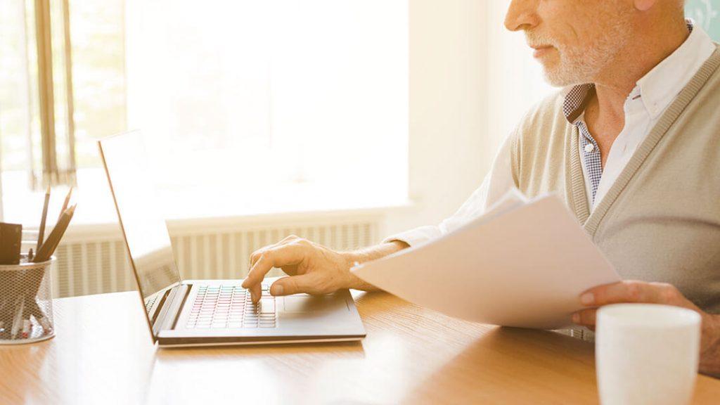 Senior devant son ordinateur. Aides aux personnes âgées